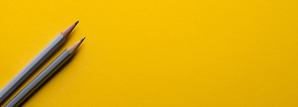 two pencils on a yellow paper background