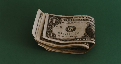 several folded dollar bills lying on a green surface