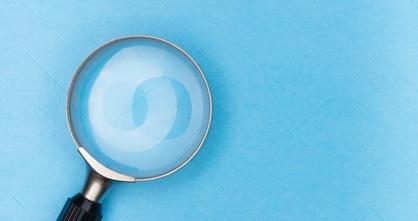 magnifying glass on light blue wallpaper