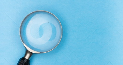 magnifying glass on light blue wallpaper