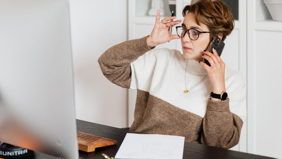 lady talking to someone over the phone at her workstation at home, and taking notes