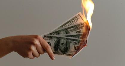 hand holding burning U.S. Dollar bills