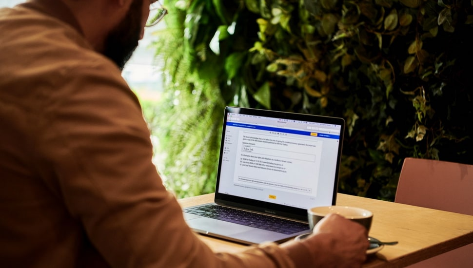 man reading contract document on laptop