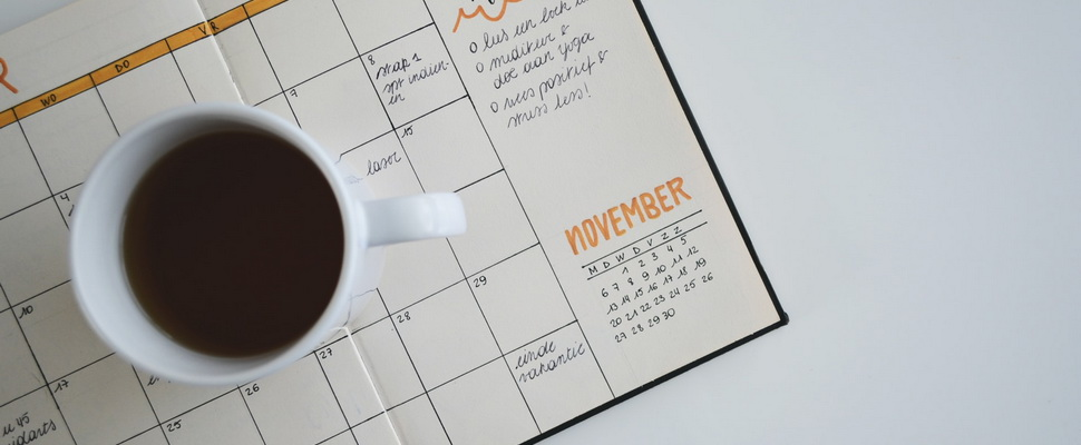 monthly planner and a mug of coffee on a white table