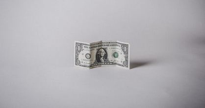 single dollar bill standing up on a grey and bleak background