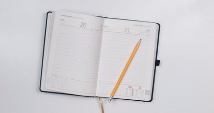 a monthly planner and pencil on a white surface